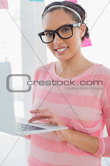 Attracative smiling artist using her laptop