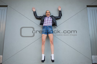 Attractive woman jumping and screaming while looking at camera