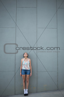 Attractive woman standing in front of a grey wall