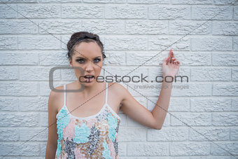 Angry woman leaning against a white wall
