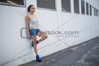 Attractive woman leaning against a wall