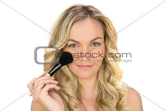 Smiling curly haired blonde using powder brush