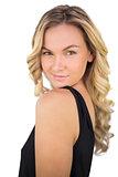 Smiling gorgeous blonde in black dress posing