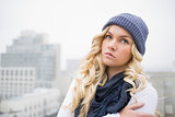 Cold blonde in winter clothes posing outdoors
