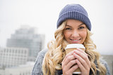 Cheerful pretty blonde having coffee outdoors