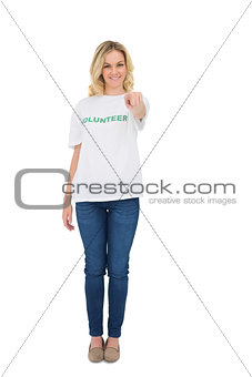 Smiling blonde volunteer pointing at camera