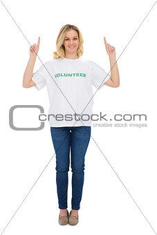 Smiling blonde volunteer pointing up