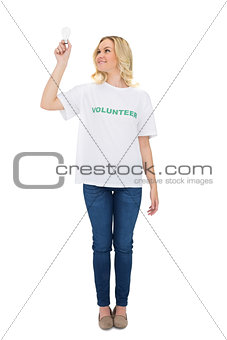 Smiling blonde volunteer holding light bulb