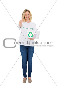 Smiling blonde volunteer holding recycling box giving thumb up to camera