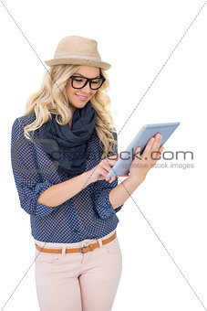 Smiling trendy blonde using tablet computer