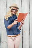 Cheerful fashionable blonde reading outdoors