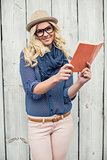 Smiling fashionable blonde holding book outdoors