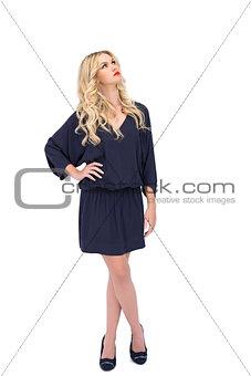 Thoughtful gorgeous model wearing elegant dress posing