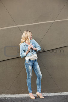 Casual blonde wearing denim clothes posing outdoors