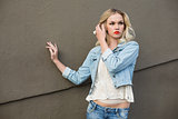 Seductive casual blonde wearing denim clothes posing outdoors