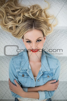 Smiling blonde wearing denim clothes lying on stairs
