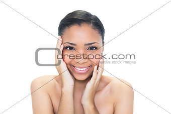 Delighted young dark haired model touching her face