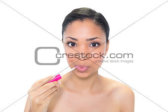 Pouting young dark haired model applying gloss