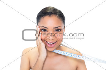 Amazed young dark haired model holding measuring tape