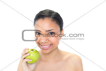 Beautiful young dark haired model holding a green apple