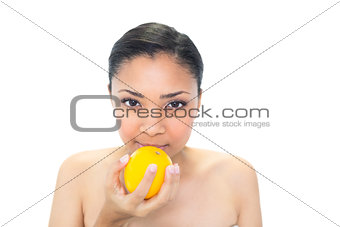Calm young dark haired model smelling an orange