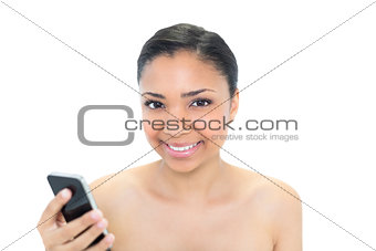 Amused young dark haired model using a mobile phone