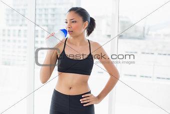 Charming dark haired model in sportswear drinking water
