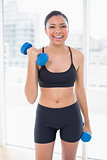 Laughing dark haired model in sportswear exercising with dumbbells