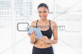 Charming dark haired model in sportswear holding a tablet pc