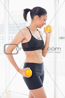 Attractive dark haired model in sportswear holding orange halves