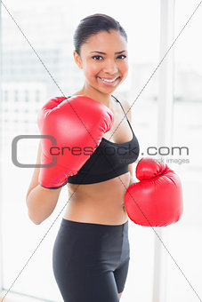 Amused dark haired model in sportswear wearing red boxing gloves