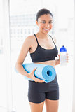 Cute dark haired model in sportswear carrying exercise mat and water