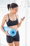 Pleased dark haired model in sportswear carrying an exercise mat and using a mobile phone