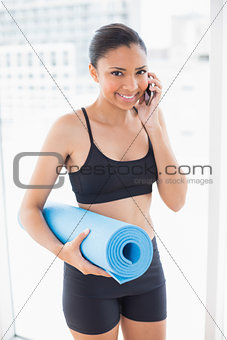 Fit dark haired model in sportswear carrying exercise mat and making a phone call