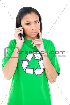 Thoughtful dark haired environmental activist making a phone call