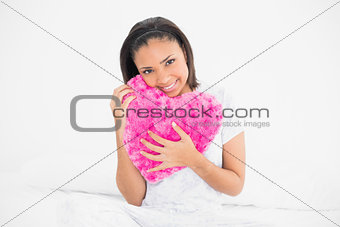 Amused young dark haired model cuddling a heart-shaped pillow