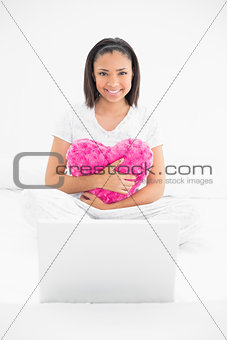 Smiling young dark haired model cuddling a pillow and using a laptop