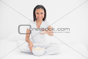 Content young dark haired model eating popcorn and changing tv channel