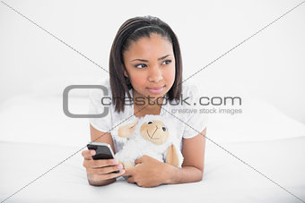 Thoughtful young dark haired model holding a mobile phone and a plush sheep
