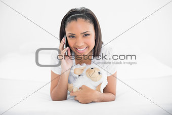 Joyful young dark haired model making phone call while cuddling plush sheep