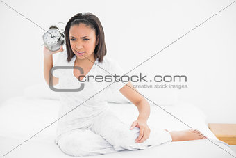 Angry young dark haired model throwing an alarm clock