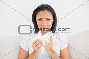 Anxious young dark haired model holding tissues