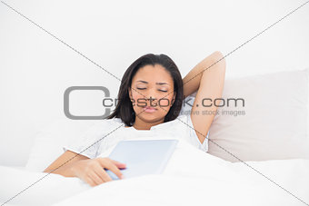 Sleepy young dark haired model holding a tablet pc