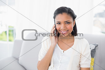 Happy young dark haired woman in white clothes making a phone call