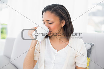 Attractive young dark haired woman in white clothes drinking coffee