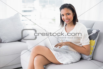 Attractive young dark haired woman in white clothes using a laptop