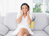 Pleased young dark haired woman in white clothes listening to music