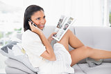 Pensive young dark haired woman in white clothes making a phone call
