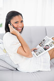 Beautiful young dark haired woman in white clothes making a phone call