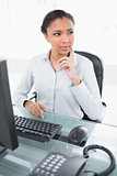 Pensive young dark haired businesswoman looking away